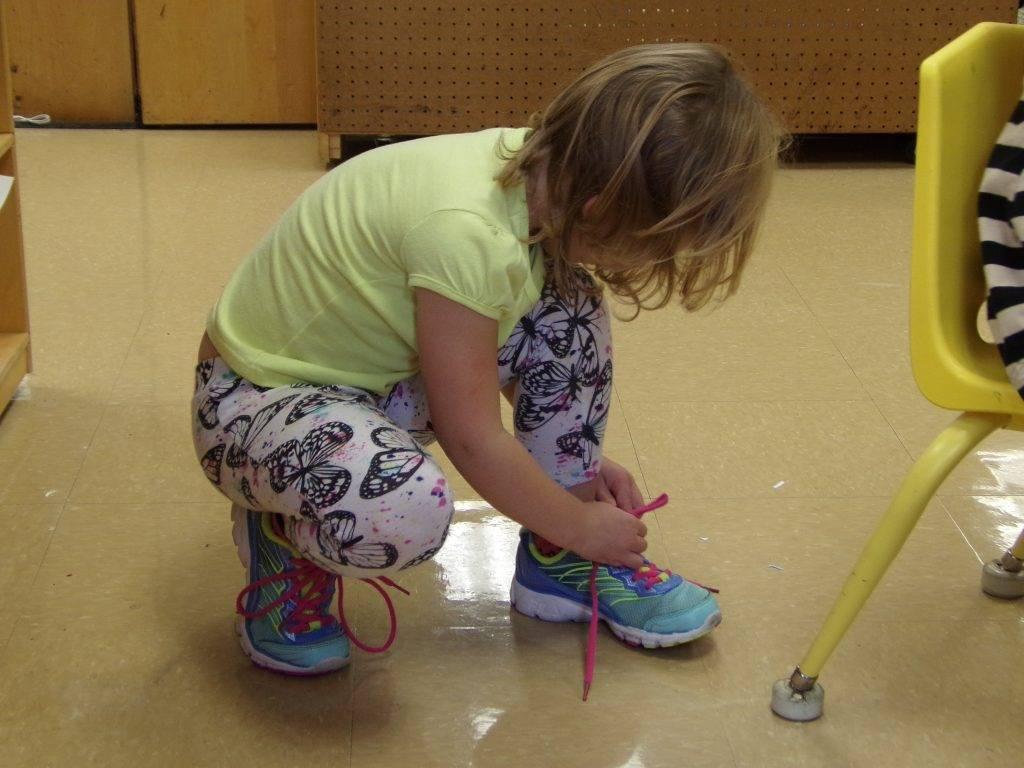 Preschooler tying shoe